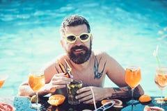 Basenu przyj?cie, witamina i dieting, Koktajl z owoc przy brodatym m??czyzn? w basenie M??czyzny napoju i dop?yni?cia alkohol Rel obraz royalty free