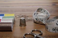 Bases de couture sur une table de couture en bois Images stock
