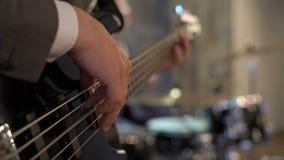 Basgitarist in de muziek van kostuumspelen met slagwerker Zwarte basgitaar met koorden en vingers, klankbekkens, trommels, hals,  stock video