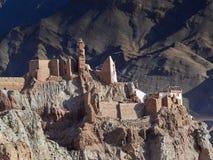 Basgo Gonpa老佛教徒修道院废墟:棕色墙壁遗骸在一座高棕色山站立,在高的背景中 免版税库存图片