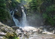 Bash Bish Falls in sun and shade. Water flows over Bash Bish Falls and into the bright sunshine royalty free stock photo
