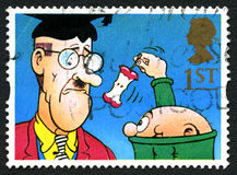 The Bash Street Kids UK Postage Stamp. GREAT BRITAIN - CIRCA 2014: A used postage stamp from the UK, depicting a scene from the Bash Street Kids comic strip stock photos