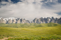 At-Bashi Mountain peaks with snow, green pastures under stormy sky in Kyrgyzstan. At-Bashi Mountain peaks with snow, green pastures under cloudy blue sky in stock photos