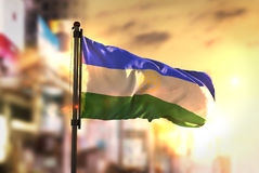 Bashkortostan Flag Against City Blurred Background At Sunrise Ba. Cklight Sky Royalty Free Stock Images