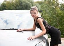 Basi della ragazza su un cappuccio dell'automobile Fotografia Stock