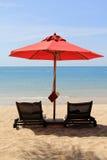 Basi prendenti il sole con un ombrello rosso Fotografia Stock Libera da Diritti