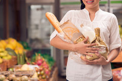 Basic food. Cropped image of a woman standing with basic food in hands royalty free stock photo