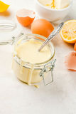 Basic Hollandaise sauce. Traditional basic sauces. French cuisine. Hollandaise sauce in glass jar, with ingredients for cooking - eggs, butter, lemons. On a Stock Images