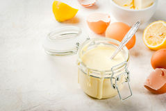 Basic Hollandaise sauce. Traditional basic sauces. French cuisine. Hollandaise sauce in glass jar, with ingredients for cooking - eggs, butter, lemons. On a royalty free stock photos