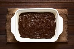 Basic Homemade Brownie or Chocolate Cake Dough. In greased and floured baking pan, photographed overhead on dark wood with natural light Stock Photography