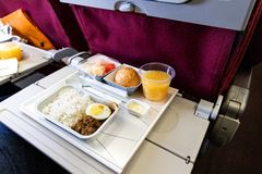 Basic inflight meal consisting rice, egg, beef curry, bread, juice. Basic inflight meal of economy class consisting rice, egg, beef curry, bread, fruits, and royalty free stock photo