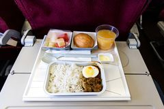 Basic inflight meal consisting rice, egg, beef curry, bread, juice. Basic inflight meal of economy class consisting rice, egg, beef curry, bread, fruits, and stock photography