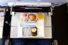 Basic inflight meal consisting rice, egg, beef curry, bread, juice. Overhead view of basic inflight meal of economy class consisting rice, egg, beef curry, bread stock images