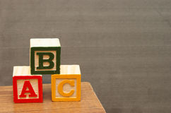 Basic Learning. Alphabet blocks in front of the chalkboard for learning the basics of the english language Stock Photo