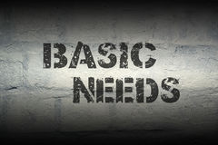 Basic needs gr. Basic needs stencil print on the grunge white brick wall; specially designed font is used stock image