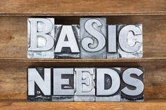 Basic needs tray. Basic needs phrase made from metallic letterpress type on wooden tray royalty free stock image
