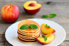 Basic pancakes with syrup and grilled nectarines on a serving plate and an old wooden table. Pancake recipe without butter Royalty Free Stock Photo