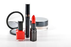 Basic red makeup cosmetics on white background. Basic red makeup cosmetics isolated on white background. Red lipstick, mascara, red nail enamel, compact travel royalty free stock images