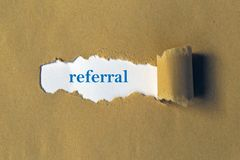 Referral heading. Behind torn brown paper royalty free stock image