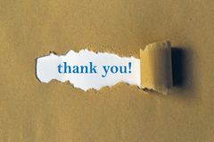 Thank you. Text 'thank you!' in blue typescript on white paper viewed through a wide slit in thicker brown paper with torn edges royalty free stock photography