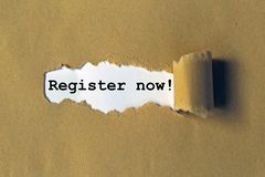 Register Now Message. A piece of kraft paper peeling back to show a hidden message telling people to register now stock photo