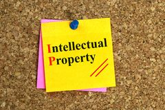 Intellectual property heading. On post-it note pinned to cork board stock photos