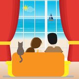 Familiy sitting on the sofa and looking on the window at a sea landscape