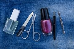Basic set of manicure tools on jeans background. Nail and cuticle scissors, cuticle trimmer, nail file, nail polish Royalty Free Stock Image