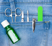 Basic set of manicure tools in jeans pocket. Basic set of manicure tools in blue jeans pocket. Nail and cuticle scissors, cuticle trimmer, nail clippers Royalty Free Stock Photography