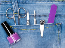 Basic set of manicure tools in jeans pocket. Nail and cuticle scissors, cuticle trimmer, nail clippers, nailfile, nail polish Stock Photo