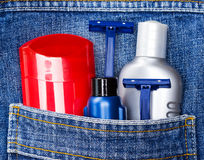 Basic skin care cosmetic products and accessories for men. Antiperspirant deodorant, shaving cream, aftershave lotion and disposable razors in jeans pocket royalty free stock photos