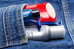 Basic skin care cosmetic products and accessories for men. Antiperspirant deodorant, shaving cream, aftershave lotion and disposable razors in jeans pocket stock photography