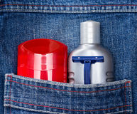 Basic skin care cosmetic products and accessories for men. Mens cosmetics. Antiperspirant deodorant, aftershave lotion and disposable razor in jeans pocket royalty free stock photo