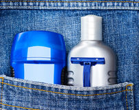 Basic skin care cosmetic products and accessories for men. Mens cosmetics. Antiperspirant deodorant, aftershave lotion and disposable razor in jeans pocket royalty free stock photos