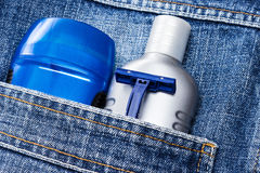 Basic skin care cosmetic products and accessories for men. Mens cosmetics. Antiperspirant deodorant, aftershave lotion and disposable razor in jeans pocket stock image