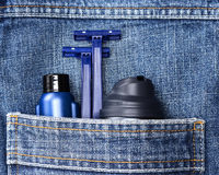 Basic skin care cosmetic products and accessories for men. Mens cosmetics. Shaving foam, disposable razors and aftershave lotion in jeans pocket. Basic skin care stock photography