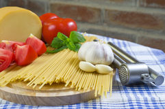 Basic Spaghetti. Raw Spaghetti with Red Tomatos and Garlic On Kitchen Table stock photo