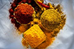 Basic spices of Indian food. Close up of three basic spices of Indian Asian food that are red pepper powder, turmeric powder and Dried coriander seed powder  on Stock Photo