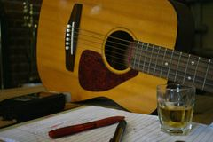 Songwriter Tools of the Trade 2. Basic tools of the trade for songwriter plus a whiskey shot for good measure. In the foreground, pens, guitar picks, and a shot royalty free stock photography
