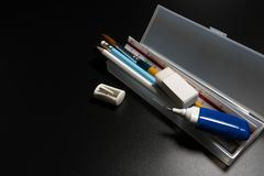 Basic white plastic pencil box with pencil, pen, eraser, sharpener and paintbrush on black background. Close up of pencil box with school supplies on black stock photography