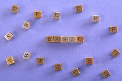 Basic word metal block. Basic word gold and silver metal block on blue paper with letter blocks around stock image