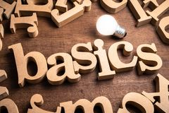 Basics Wood Word. BASICS word in scattered wood letters on the table with glowing light bulb royalty free stock photos
