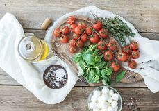 Basil, cherry-tomatoes, mozarella, olive oil, salt, spices on rustic chopping board Royalty Free Stock Photo