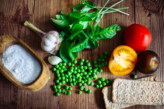 Basil, color tomatoes, garlic, green peas and two crispbread Stock Photos