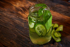 Basil cucumber home-made lemonade on rustic background in mason jars Stock Images
