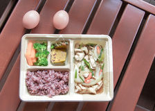 Basil fried rice in foam box on wood background Stock Images