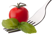 Basil leaf  and cherry tomato on fork isolated on white backgrou Royalty Free Stock Photos