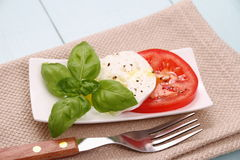 Basil leaf, mozzarella cheese, tomato slice, fork Stock Photos