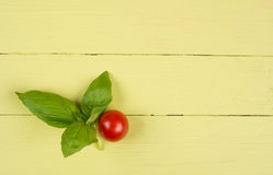 Basil leaves and tomato on yellow table Royalty Free Stock Photography