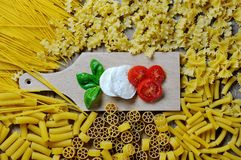 Basil, mozzarella and tomato on chopping board, and italian pasta stock photography